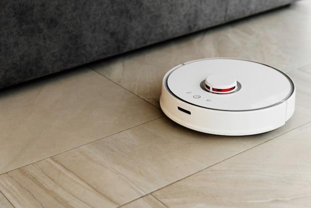 Aspirapolvere robot bianco sul pavimento
