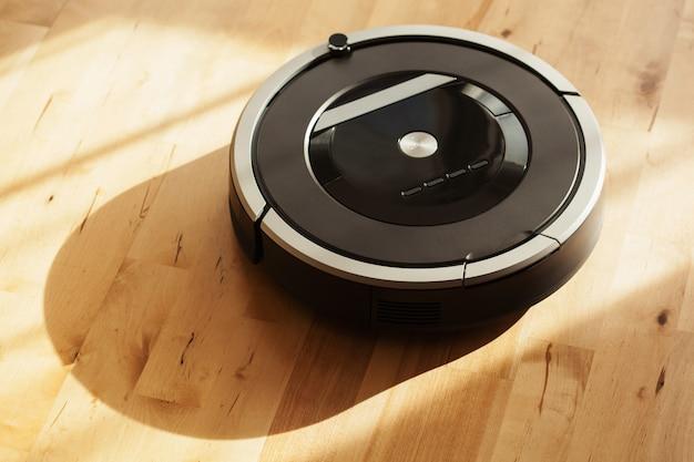 Aspirapolvere robot sul pavimento in legno laminato