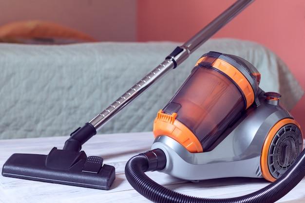 Aspirapolvere su uno sfondo di camera da letto
