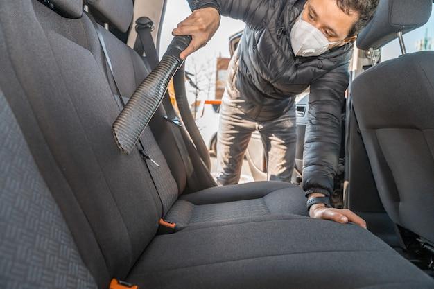 Aspirare l'interno di un'autovettura usando un aspirapolvere industriale. l'uomo lavora in mascherina medica protettiva. protezione contro il coronavirus