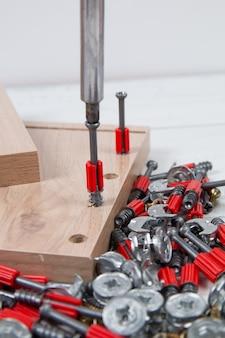 Assemblaggio di mobili con un cacciavite. assemblaggio di mobili. accessori per mobili e elementi di fissaggio.