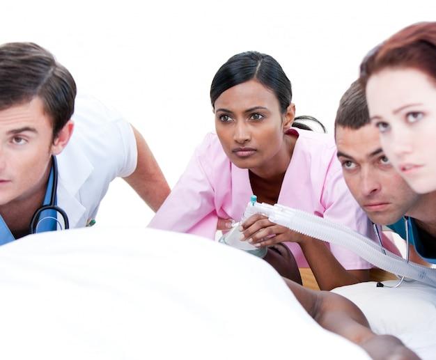 Assertivo team medico multietnico che rianima un paziente