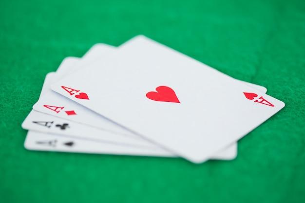 Assi di carte da gioco su tappetini verdi