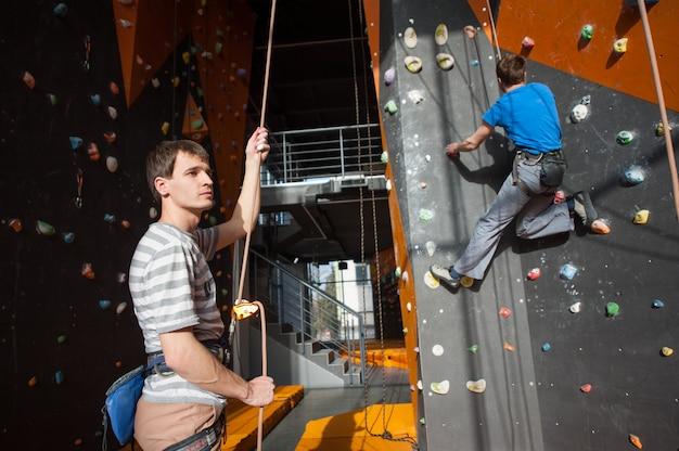 Assicuratore che assicura lo scalatore sulla parete di roccia al chiuso