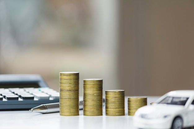 Assicurazione auto e servizio auto. grafico a linee con la pila di monete e concetto dell'automobile, di affari e finanziario del giocattolo.