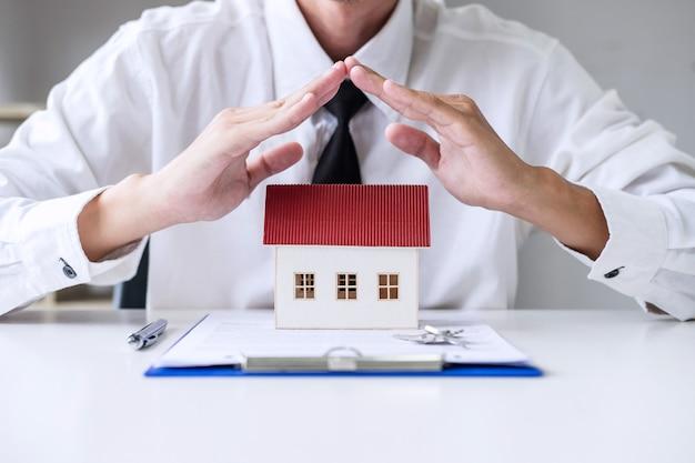 Assicurazione e protezione di cura del concetto di casa, agente di uomo d'affari con gesto protettivo