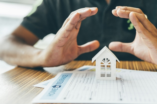 Assicurazione sulla casa o protezione della proprietà. agente assicurativo completo, casa modello in legno sul denaro.