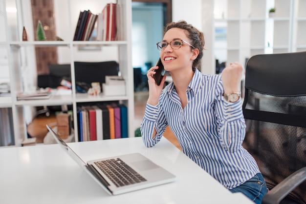 Assistente amministrativo femminile sorridente che comunica sul telefono nell'ufficio, ricevente le buone notizie.