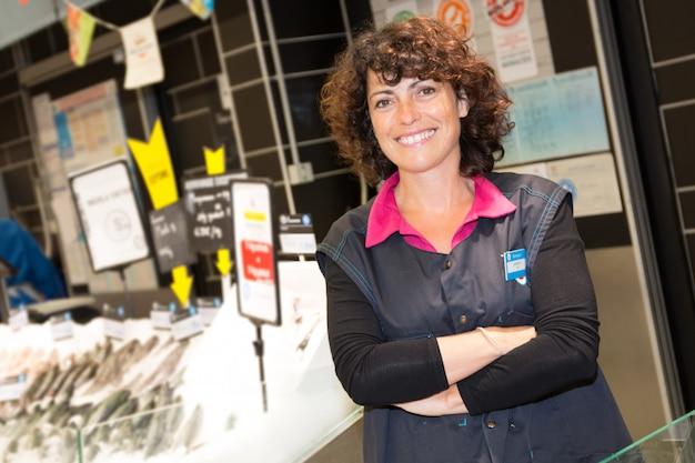 Assistente della donna del venditore in supermercato che vende pesce fresco al negozio