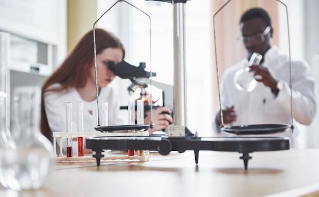 Assistente di laboratorio con lampadina di vetreria di laboratorio microscopio con prodotti chimici.