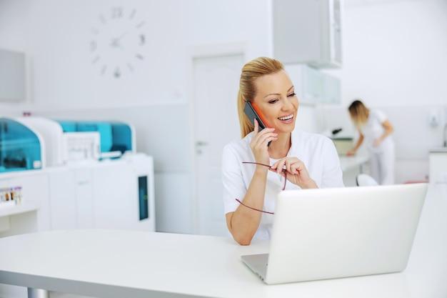 Assistente di laboratorio sorridente bionda attraente educato seduto in laboratorio, avendo telefonata con il paziente e guardando il laptop con i risultati dei test
