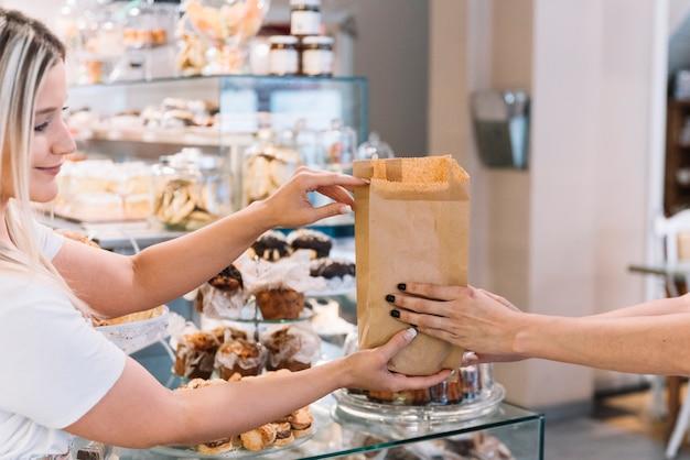 Assistente di negozio che dà la borsa del croissant