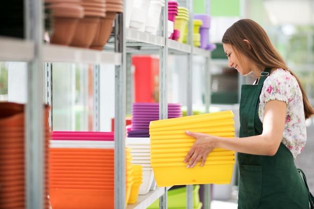 Assistente di negozio presso gli scaffali di carico di un asilo nido