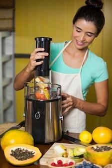 Assistente di negozio sorridente che prepara il succo