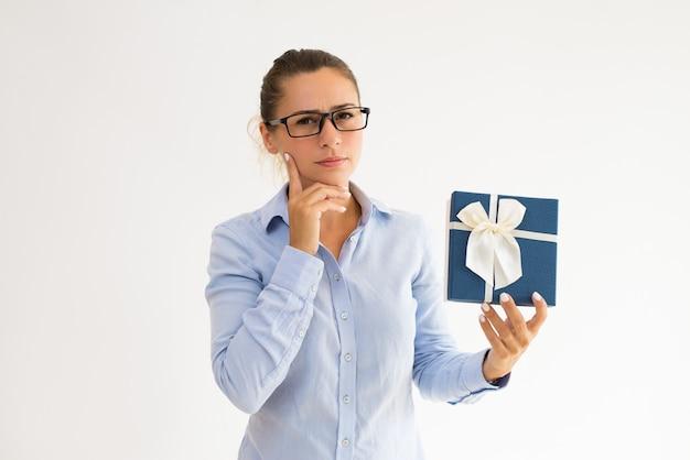 Assistente di ufficio pensoso aggrottante le sopracciglia che pensa sopra il regalo corporativo