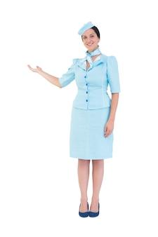 Assistente di volo abbastanza che mostra con la mano