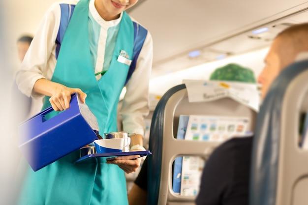 Assistente di volo che serve bevande ai passeggeri a bordo.