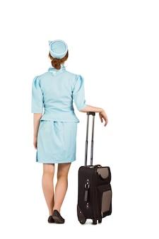 Assistente di volo graziosa che si appoggia sulla valigia