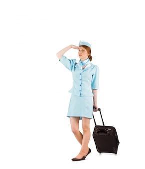 Assistente di volo graziosa che tira valigia