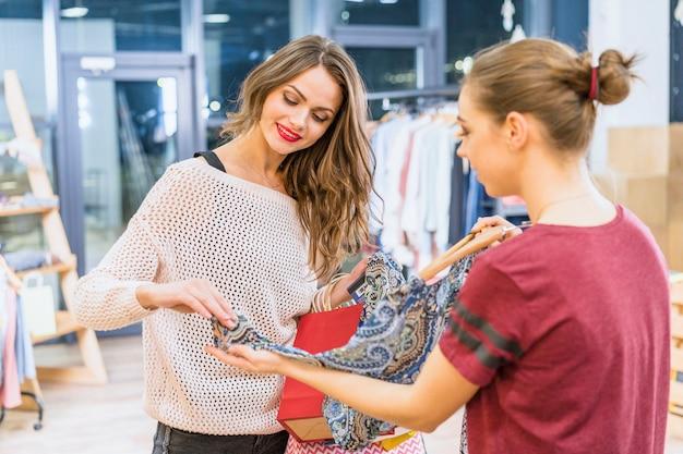 Assistente femminile positivo che serve giovane cliente in boutique di abbigliamento