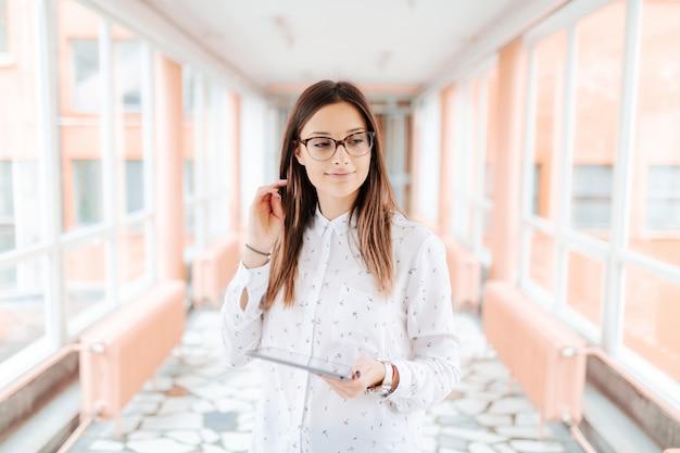 Assistente femminile sorridente dei giovani con gli occhiali e la compressa della tenuta dei capelli marroni e capelli commoventi mentre stando nel corridoio.