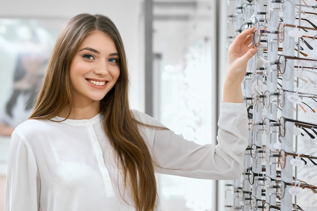 Assistente ottico amichevole sorridente in gabinetto oftalmologico.