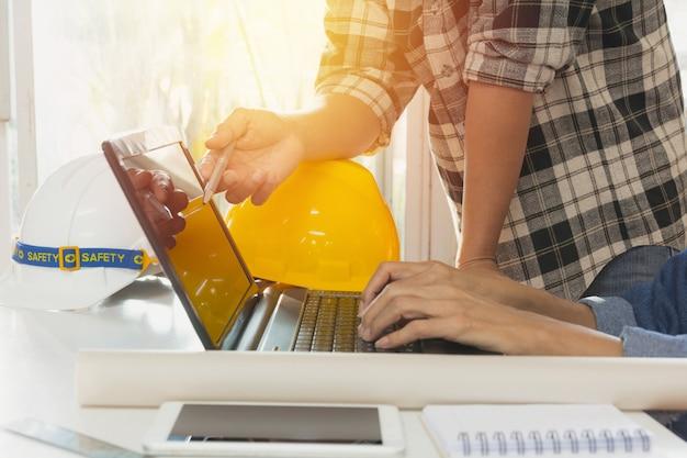 Assistente tecnico dell'architetto che per mezzo del computer portatile per lavorare con il casco e il computer portatile gialli sulla tavola.
