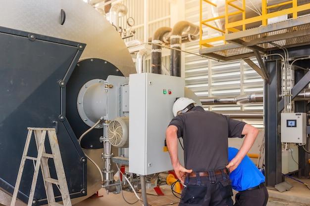 Assistente tecnico di manutenzione che lavora con la caldaia a gas dell'apparecchiatura del sistema di riscaldamento in un locale caldaie