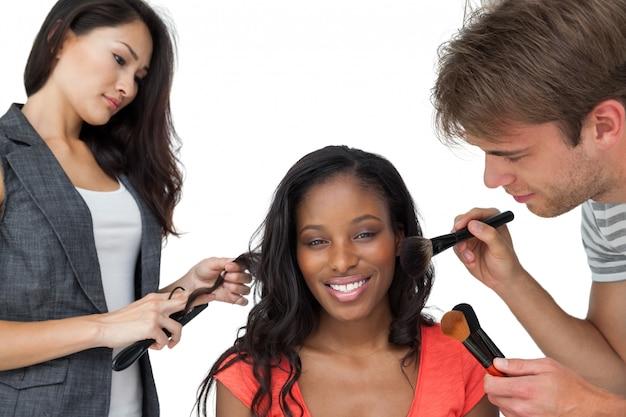 Assistenti che applicano il trucco a un modello femminile