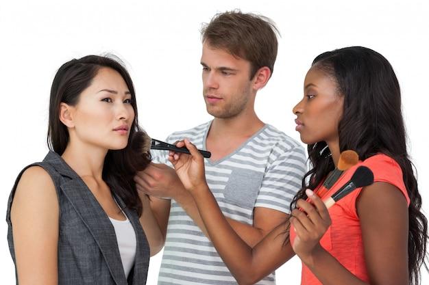 Assistenti che applicano il trucco al modello femminile