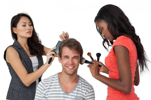 Assistenti che applicano il trucco al modello maschio