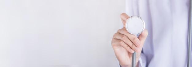 Assistenza sanitaria con stetoscopio della holding della mano del medico