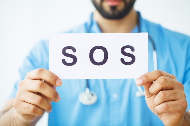 Assistenza sanitaria. il dottore holding una carta con sos, concetto medico