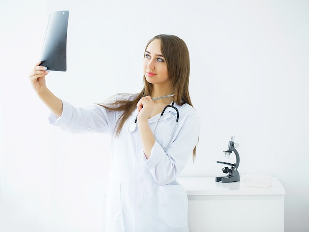 Assistenza sanitaria. ritratto del rapporto dei raggi x di examining dell'infermiera femminile.