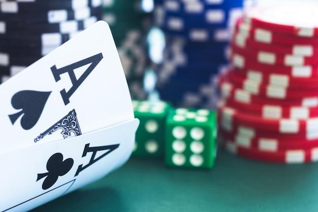 Asso di poker su pile di fiches e dadi