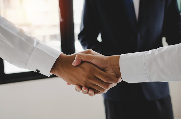 Associazione. gruppo di stretta di mano della gente dell'investitore di affari dopo la riunione d'affari nella sala riunioni all'ufficio