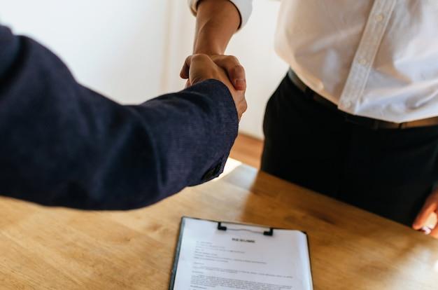 Associazione. uomini d'affari si stringono la mano dopo la firma del contratto di lavoro e riprendono sulla scrivania nella sala riunioni presso la sede dell'azienda, colloquio di lavoro, investitore, negoziazione, partenariato e concetto di lavoro di squadra