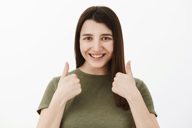 Assolutamente sicuro che ti piaccia. cliente femminile soddisfatto ottimistico fiducioso e amichevole che mostra i pollici in su nel gesto di approvazione e di raccomandazione che sorride felice di ricevere un prodotto di buona qualità
