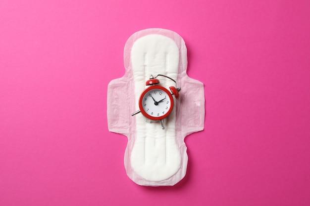 Assorbente con sveglia sulla superficie rosa