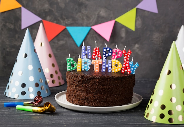 Assortimento con torta di compleanno e cappelli da festa
