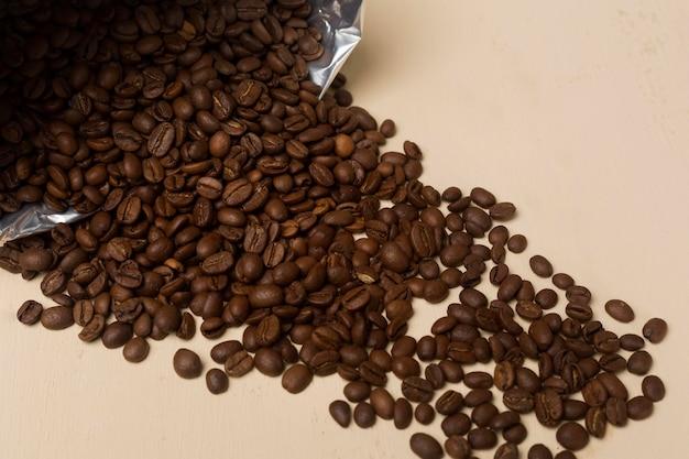 Assortimento dei chicchi di caffè nero su fondo beige