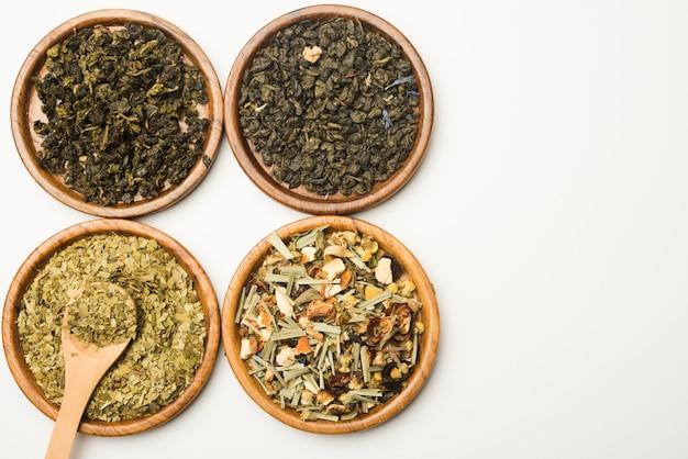 Assortimento dei piatti circolari di legno delle erbe medicinali asciutte sul contesto bianco