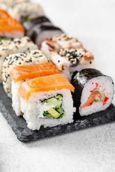 Assortimento dei rotoli di sushi di maki del primo piano sull'ardesia