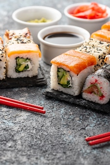 Assortimento del primo piano dei rotoli di sushi di maki con le bacchette