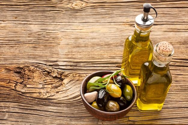 Assortimento dell'angolo alto di olive variopinte con la bottiglia di olio e lo spazio della copia