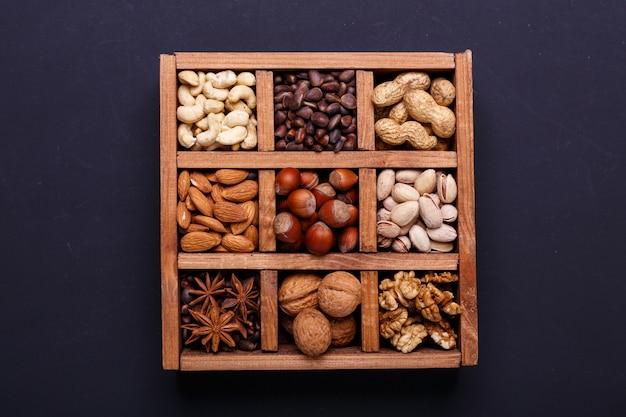 Assortimento delle noci in una scatola di legno su un'ardesia nera - spuntino sano.