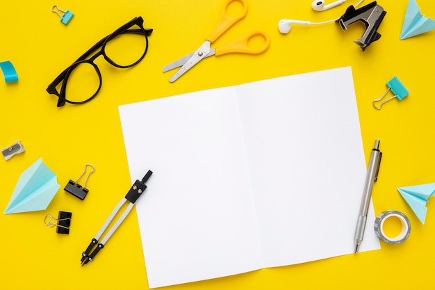 Assortimento di articoli di cancelleria vista dall'alto su sfondo giallo
