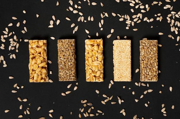 Assortimento di barre di cereali piatto laici con semi di girasole su sfondo chiaro