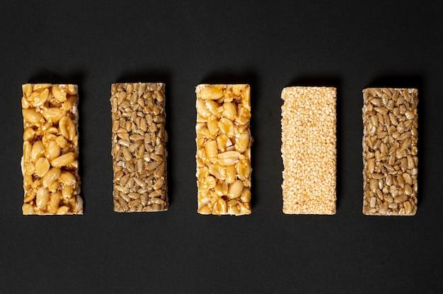 Assortimento di barrette di cereali distesi su sfondo chiaro
