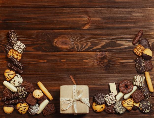Assortimento di biscotti misti ricoperti di cioccolato in prossimità di confezione regalo